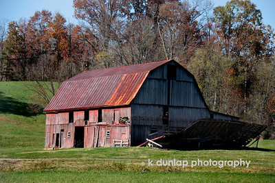 "11.13.09 = Things that make you think twice.  I came across this old barn the other day in my travels. I'm still trying to figure it out.  At first glance it looks as if the wall fell off, however the inside of the wall is facing the ground, so that couldn't be.  Then you assume it was another structure built right next to the barn…could be…Like I said, I'm still thinking about it.    ""Diplomacy is thinking twice before saying nothing.""  Unknown"