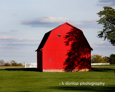 "10.14.09 = Dancing shadows.  I loved how the shadows of the leaves danced on the side of this bright red barn.  Bright blue skies, red barns, green grass and white fences.....perfect comp for photo don't you think?  Sorry I've missed posting for a few days but I've been out of town and running like a mad woman.  Is it Friday yet?   ""Keep your face toward the sunshine and shadows will fall behind you.""  Walt Whitman"