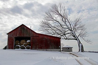 "02.26.10 = Snow on the farm  Some of you may remember this shot from last fall.  http://kdunlap.smugmug.com/Photo-Journal/2009-Through-my-eyes-Photo/7225906_AuSgs#712743069_NmThi I loved the composition of the shot however, I was shooting in such bright direct sunlight, that I couldn't get a really good shot of it.  I've always felt that I didn't do the scene justice.  I still love how that tree just curves into the barn as to protect it from the weather.  Like a good friend watching over you.    ""True friendship comes when the silence between them is comfortable.""  Unknown"