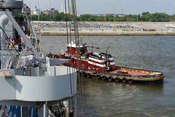 Tugboat moves us into position for docking.  You can see the towline pulling the bow of the ship in a clockwise direction.