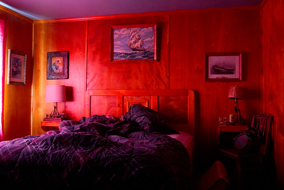 Hannah lazily welcomes the morning.  The light appears to be filtered or altered, but the sunshine through the red curtains and the wood paneling reflecting that light  provide these warm and dreamy colors.