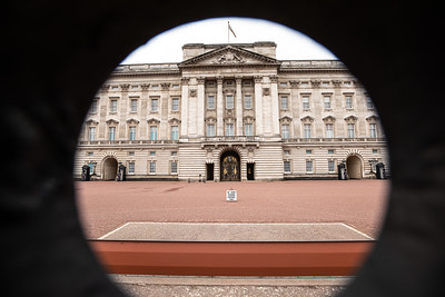 A shot of the palace and guards through a circular hole in the perimeter fence.
