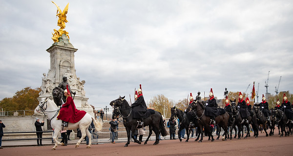 The mounted patrol passes in between the Victoria Memorial and Buckingham Palace.