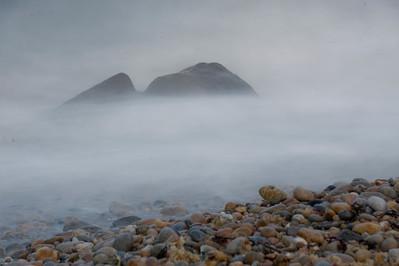 Crashing surf shrouds rocks, Montauk Point.
