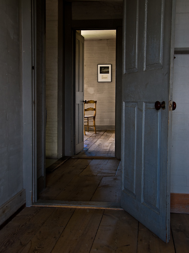 View of a chair through a doorway in the Olson House in Cushing, Maine.
