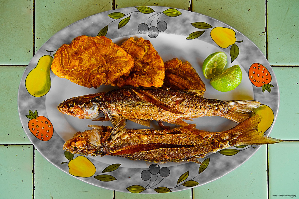 Lisa frita con Patacones en Mesa de Cerámica / Deep fried fish and plantains on ceramic tile table<br /> <br /> I couldn't think of a best thing to get my own Book of Maracaibo started. This is what folks from the city love, is a local fish from Maracaibo Lake, plantains is a must ... the part I don't get is the lime, it practically kills the flavor of the fish so why bother?<br /> <br /> Anyways, you eat this @ 40 degrees celsius (like 104 farenheit) under the shade provided by a tin roof (that acts like a heat amplifier), so in order to stay alive you ask for a cold beer ...<br /> <br /> Processed with CS4 to remove distortion and add lots of textures using the highpass filter.