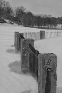 20130217.  Fence around Minute Man statue on west side of Concord River in Minute Man NHP.  Snow blowing around on very windy day.