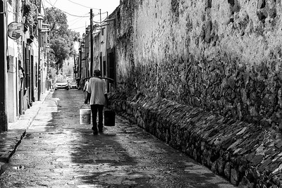 Man carrying buckets down an alley, Mexico