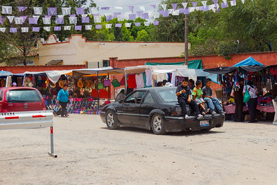 Children riding on trunk of car, Mexico