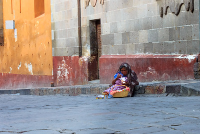 Old poor woman eating while selling handmae toys, Mexico