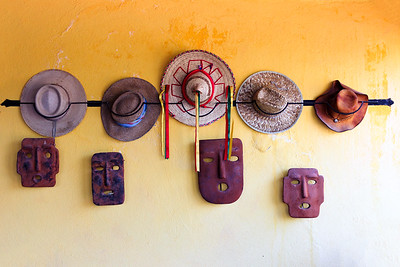 Hats hanging on a wall with Mexican decorations underneath