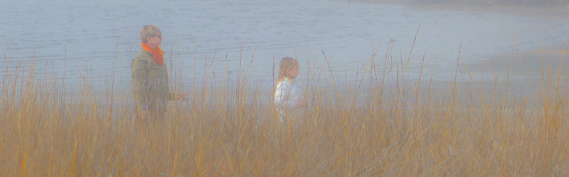 Granddaughter and Grandma strolling along the foggy shore.