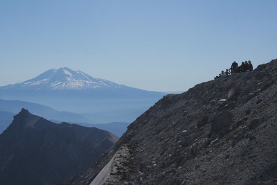 7/26/2006 9:20:14 AM  Hikers sitting on the edge of the volcano crater rim after a good hike.  The seriated edge of the rim trails to the left towards the north under the watchful eye Mt. Adams.