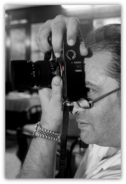 "4th year Pic 019 - Nov 18 2011 <span style=""color:yellow"">Friend Sharookh, the Leica man! </span> This was shot at Kyani restaurant.   Sharookh's fav camera is Leica and he takes great portraits. His one shot is put up in the arrival lounge of Mumbai's airport! He also loves wildlife photography which he covers with his Nikons.  You can see some of his pics at Facebook. I'd posted his pic of of Jay, Lakshmi & Anika at the Daily: <br> http://hershy.smugmug.com/Photography/Daily-third-year/12987576_xZH9v2#1501801183_f6HPPgN Here are some more of his pics - from 8 to 12<br> http://hershy.smugmug.com/Family/Anika/First-days-at-hospital/19063399_2CKq7L#1501801183_f6HPPgN <span style=""color:red"">Added later: </span>  The camera is Leica M9, a digital camera.  <span style=""color:cyan"">I am away for the weekend so won't be posting or commenting. Have a nice weekend! </span>"