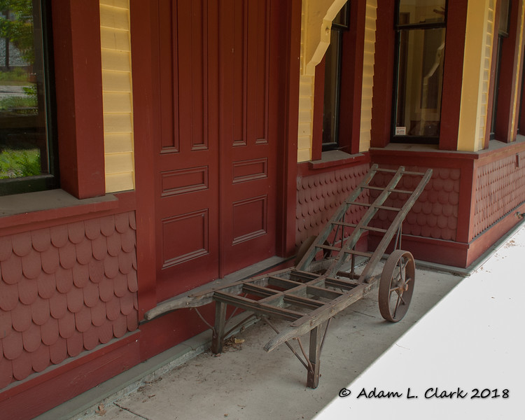 An old (possibly luggage?) cart next to the depot