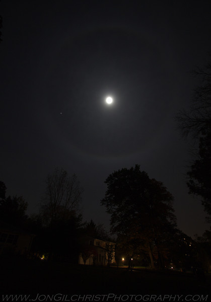 I can feel it coming in the air tonight....<br /> <br /> Ice crystals in the upper atmosphere cause light to refract. With the moon, this manifests as a ring around the moon. With the sun it causes Sun Dogs or Parhelia.  That bright spot at about 8 o'clock is Jupiter.