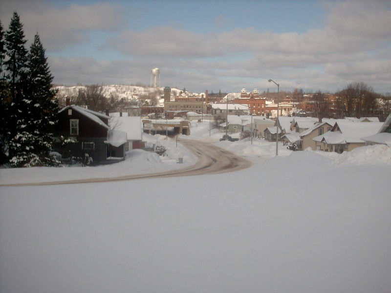 <b>Downtown Negaunee Skyline (winter)</b> - The same as the previous shot only the middle of winter. As of the date this photo was taken we'd had about 183 inches of snow so far for the season with a snowdepth right around 40 inches or so. Fairly average for that time of year. 3-2-05