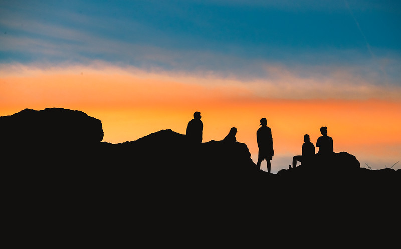 Hikers sitting, watching the sunset in Torrey Pines State Reserve.