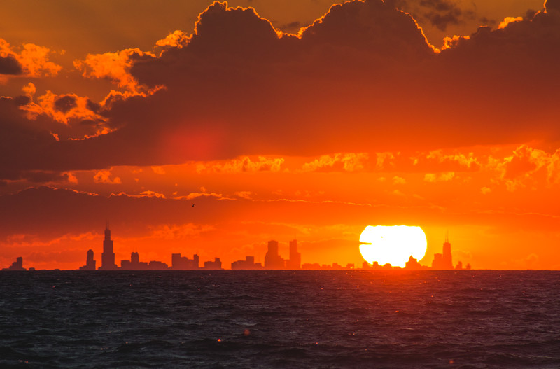 The sun within the Chicago skyline, viewed from near the Indiana Dunes State Park (Porter Beach) in mid-July.
