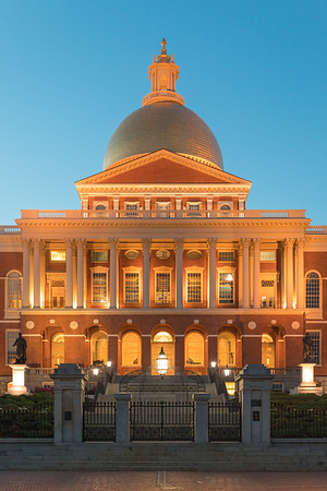 The warm architectural lighting rises as the sun sets, from the Massachusetts Statehouse.