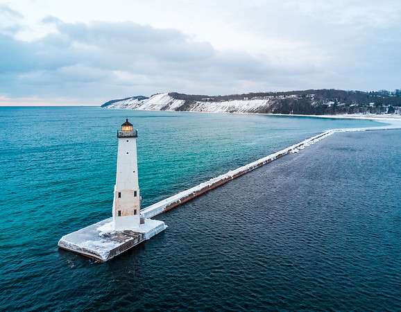 Aerial of the Frankfort North Breakwater Light showing the color change of the Lake Michigan (right, light) and Frankfort Harbor (left, dark) water - March 14th, 2017