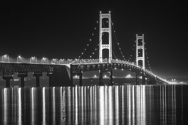 """The """"Mighty Mac""""  reflecting off the straits of Mackinac at midnight."""