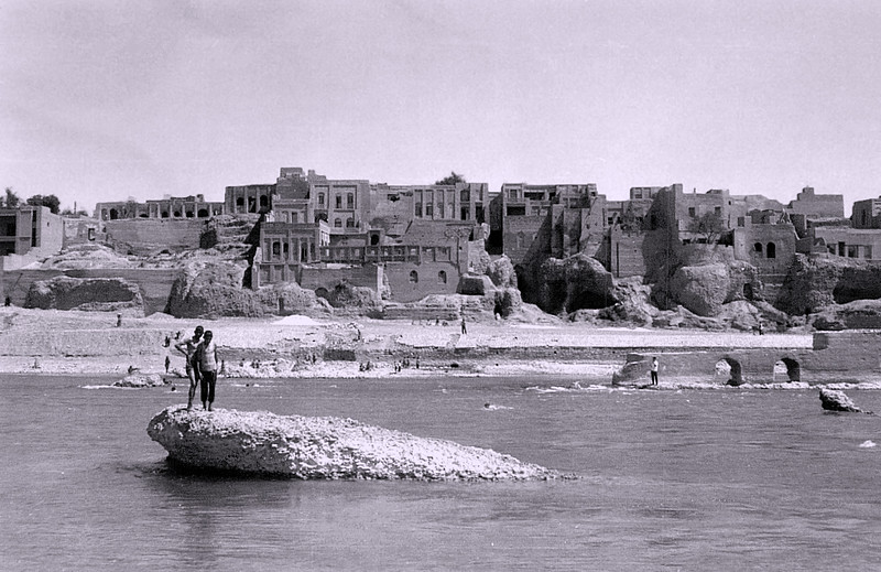 Iranian boys on river rock with village on far shore.