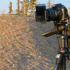 "Camera all set up for hours of sunset shots. (Next 4.)<br><br><span class=""subcaption"">&nbsp;Note the 2 stacked Cokin graduated gray filters (square) and the external remote shutter release. I've realized since this trip why even more expensive tripods are—well—more expensive. It was so windy that most of my longer-exposure shots are a teeny bit blurry from the camera moving so slightly. The remote shutter release (hanging down on the side) came in handy though. For some shots I programmed it to just take another shot every 5 minutes while I sat in the much warmer car for part of the time.</span>"