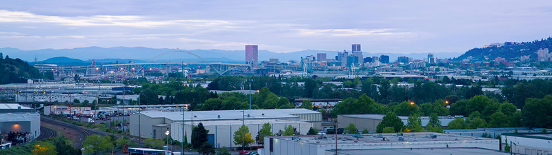 Panorama stitch of 3 photos taken from the roadside on the hills above the north side of the Willamette River at dusk. Distant is downtown Portland and the Fremont Bridge. Foreground is much of the shipping and related industry that makes Portland a <i>port</i> town.
