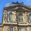 Statues holding each other as if for warmth on the Louvre (with minor water splotch)