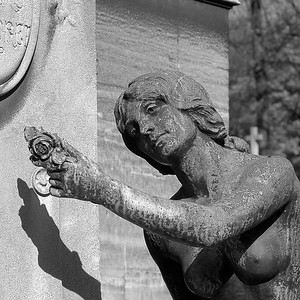 Statue of female nude holding flower, Pere Lachaise cemetery, Paris