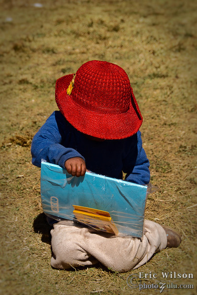 """Youngster explores a new notebook and Crayons.<br><br><span class=""""subcaption"""">(A group unrelated to Hope Projects also came to the village the same day. They had collected money to donate small amounts of school supplies to the villagers.)</span>"""