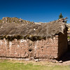 A typical village family dwelling with thatch roof and adobe bricks.