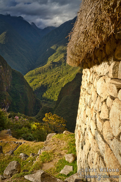 "Common dwelling, Machu Picchu. &nbsp;<br><br><span class=""subcaption""> (The reconstructed roof is in the fashion scholars believe original inhabitants would have done. Note the slanting walls that were common in their dwellings. Urubamba river canyon below.)</span>"