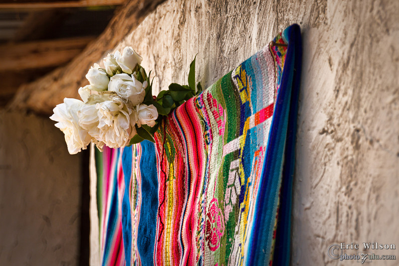 "Plaque covering  <br><br><span class=""subcaption"">(Dedications usually involve breaking some flask of chicha and then uncovering the Hope Projects sponsorship plaque embedded in the wall. For the villagers the flowers and blanket is showing off their best.)</span>"