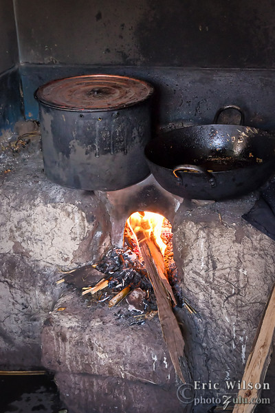 "One of the nicer indoor cooking configurations. <br><br><span class=""subcaption"">(One of the Hope Project's common projects is to replace the traditional in-room fire cooking with a ""smokeless stove"" which reduces the locals' lung problems considerably.)</span>"