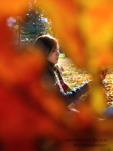 A student plays in the leaves.