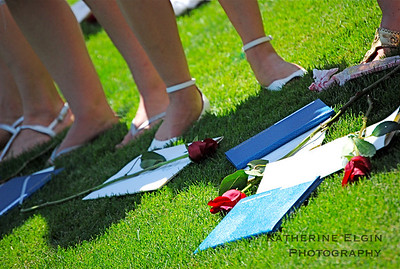 Girls place their diplomas and roses on the ground as they pass their classmates' diplomas around the receiving circle.