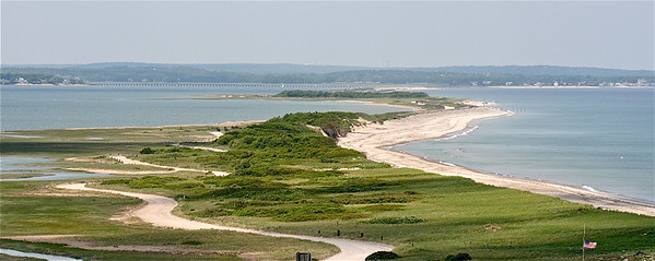 A view from the top of the Gurnet Lighthouse looking back toward Duxbury.  The Gurnet road snakes its way along the left side of the peninsula.  The Power Point Bridge can be seem in the background.