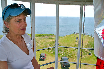 """Dolly Bicknell, President of """"Project Gurnet & Bug Lights,"""" concludes her tour within confines of the glass enclosed Optics Section at the top of the Gurnet lighthouse.  Holly is the daughter of author and New England Coastal Historian, Edwin Rose Snow.  He was also famous for carrying on the tradition the """"Flying Santa"""" for over forty years (1036-1980. Every Christmas he would hire a small plane and drop wrapped gifts to the lighthouse keepers and their families."""
