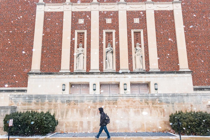Student walking through campus as snow begins to fall at Purdue University on January 29th, 2017.
