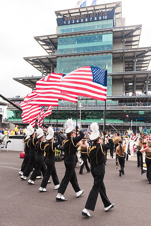 """Purdue """"All-American"""" Marching Band crossing the yard of bricks with the Borg-Warner Trophy at the Indianapolis Motor Speedway."""