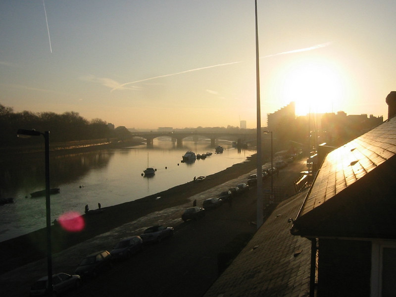 Looking off the balcony at Imperial College Boathouse as the sun rises reflecting of the roof of Thames Rowing Club.