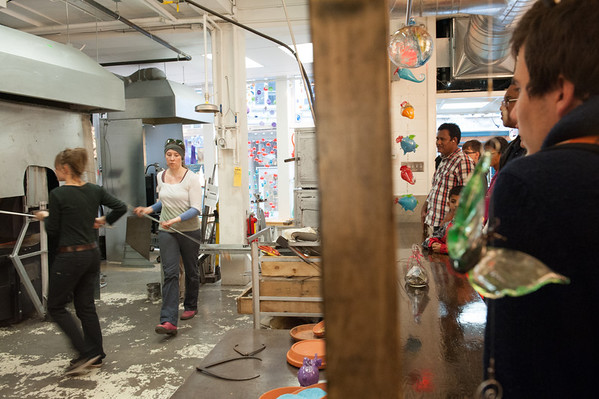 A small crowd of tourists watch glass blowers at work in their workshop in the Quartier Petit Champlain in the lower city.
