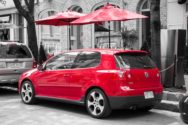 The sight of this red car parked in front of red cafe umbrellas caught my eye.
