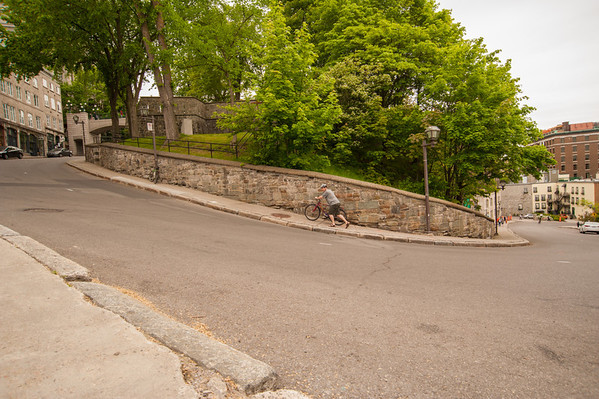The Cote de la Montagne, seen here, is one of the streets connecting the Upper Old City (to the left) with the Lower Old City (to the right).  Note the cyclist pushing his bike up the steep grade.