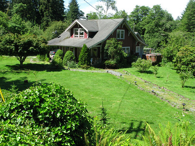 Seen from near the barn, the upper yard nestles the house in greenery. The house has five bedrooms and 2.5 baths. The large kitchen and dining area opens onto the deck overlooking the river.