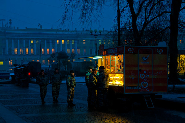 Russian soldiers are drawn to the light of the coffee stand outside the Winter Palace in the cold and snowy pre-dawn morning of St. Petersburg.            Photo by: Stephen Hindley ©