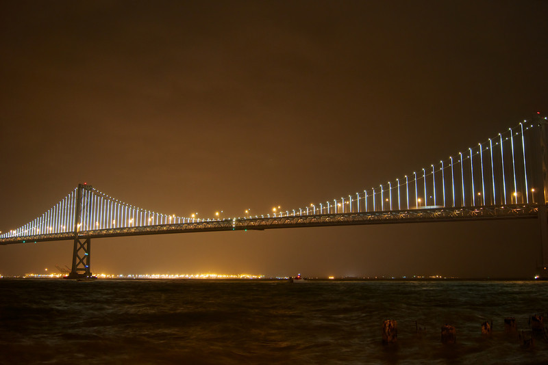The Bay Bridge lights shining bright. I captured this photo in the rain. Notice the choppy waters.