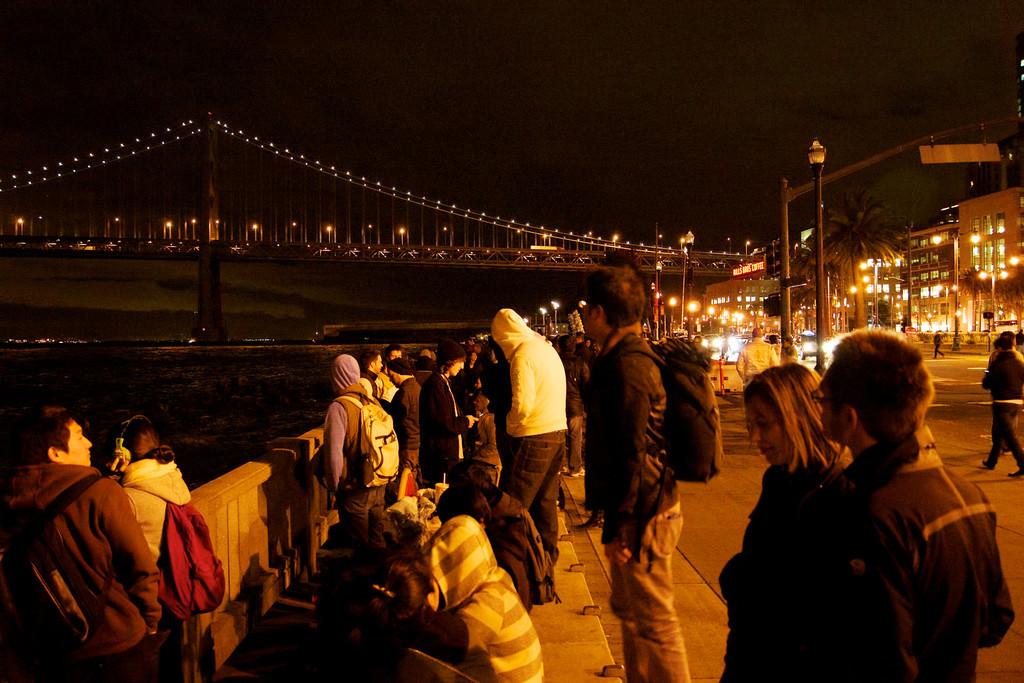Crowds line up along the San Francisco Embarcadero to view the Bay Bridge Lighting Ceremony. ref: 4e8cfd66-e90c-4a88-9264-0c518eb10476